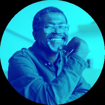 Older man wearing glasses smiling at camera.