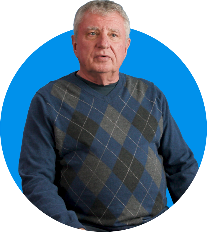 Man sitting and talking, wearing argyle sweater